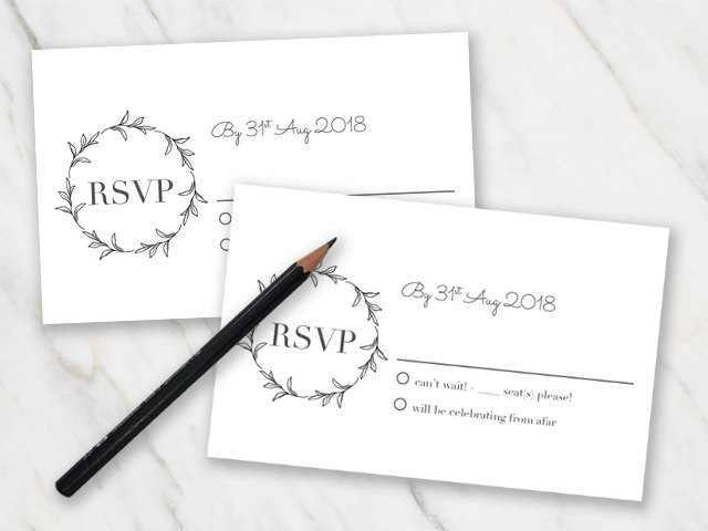 Example of two wedding rsvp cards laying on a marble table with a pencil